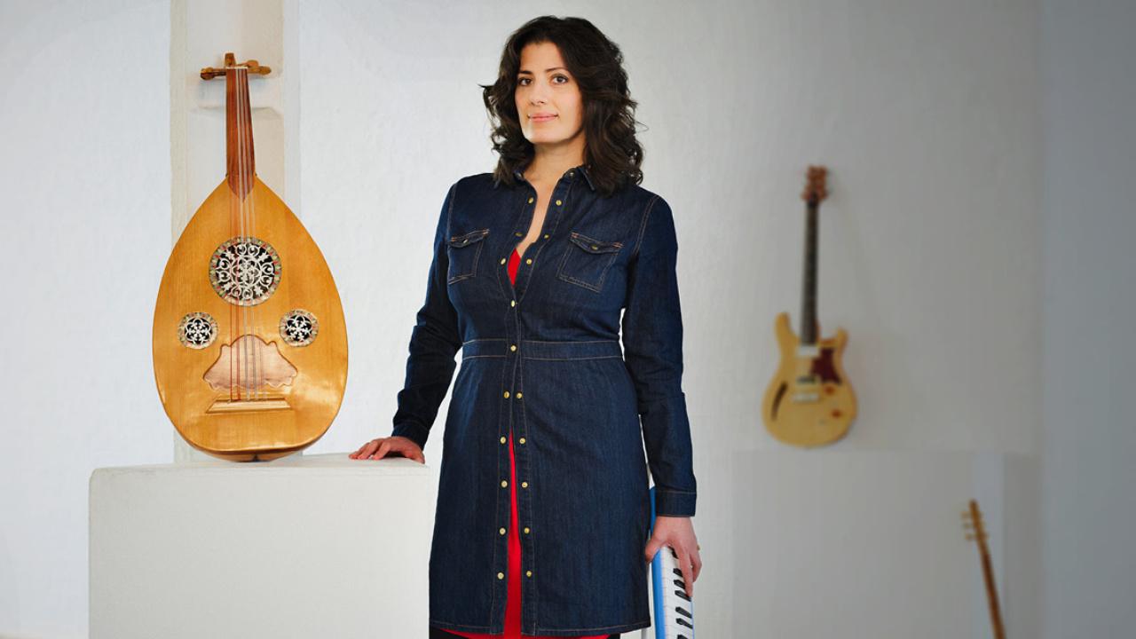 Bushra stands with her instruments around her