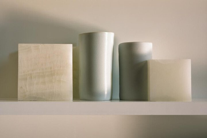 Two sculpted cubes surround two cylindrical objects