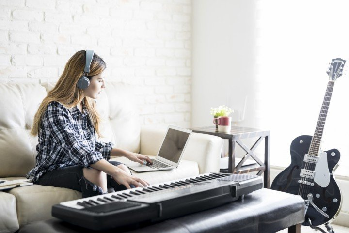 woman playing keyboard with headphones