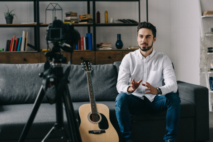 male musician filming with guitar