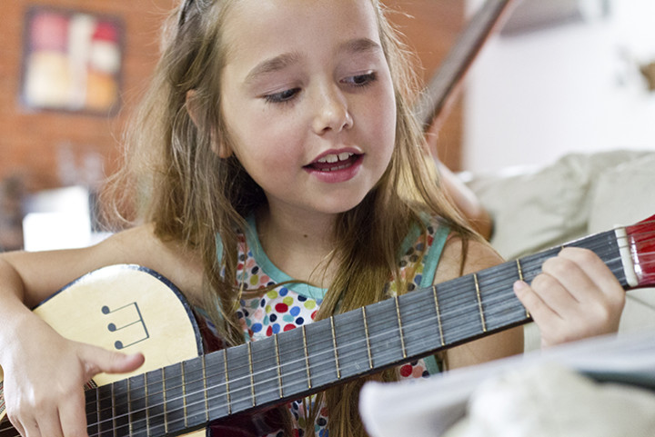 A young girl is playing the guitar.