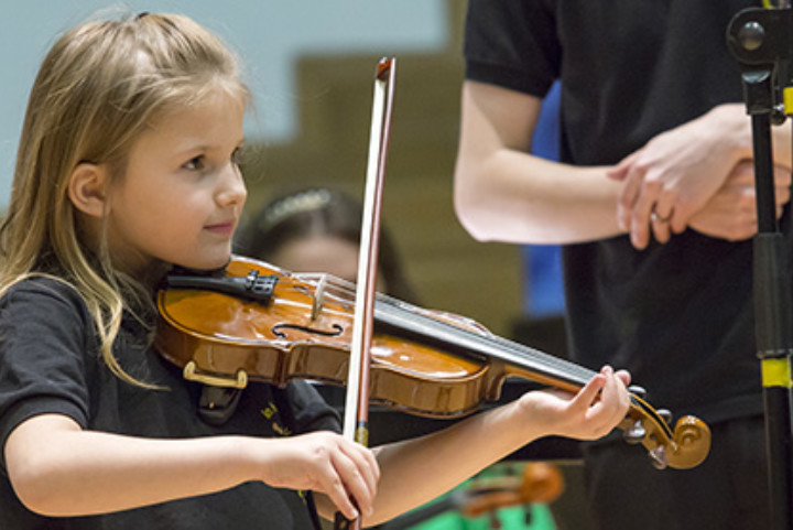 A small girl playing the violin