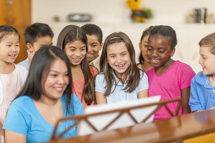 Teacher on piano with students surrounding her