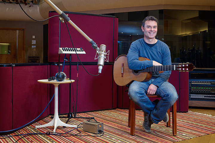 Male musician in recording studio with guitar
