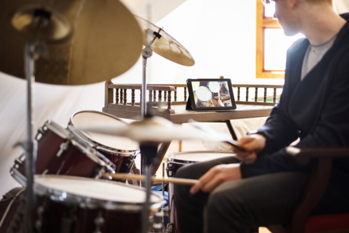 A teenage boy on a drum set with a video lesson showing in the background