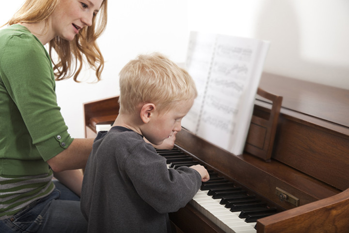 Teacher gives piano lesson to key stage one child