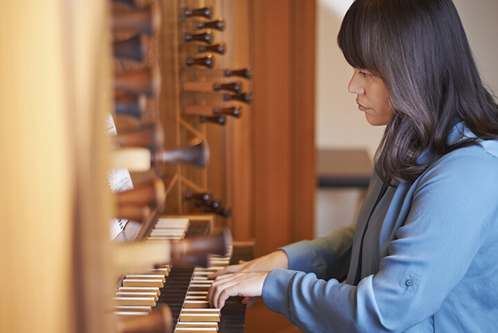 Young female playing the church organ