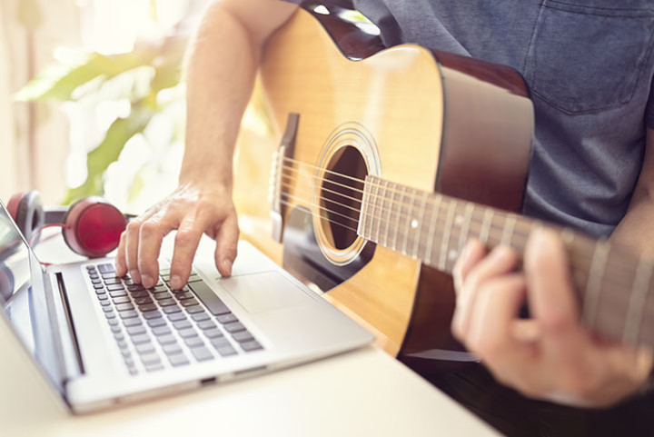 Man plays guitar next to his laptop