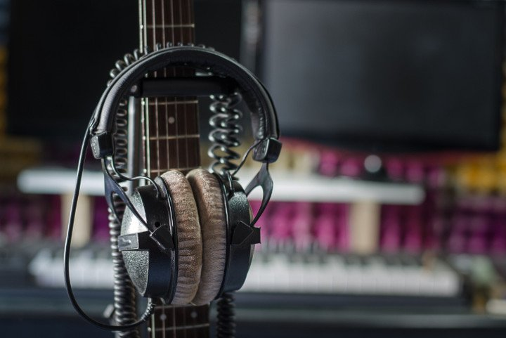 Headphones resting on a capo on the fretboard of a guitar.