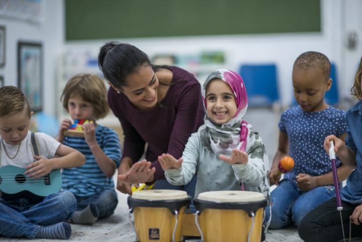 Women teaching young children