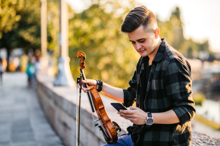 A male violinist looks at his phone