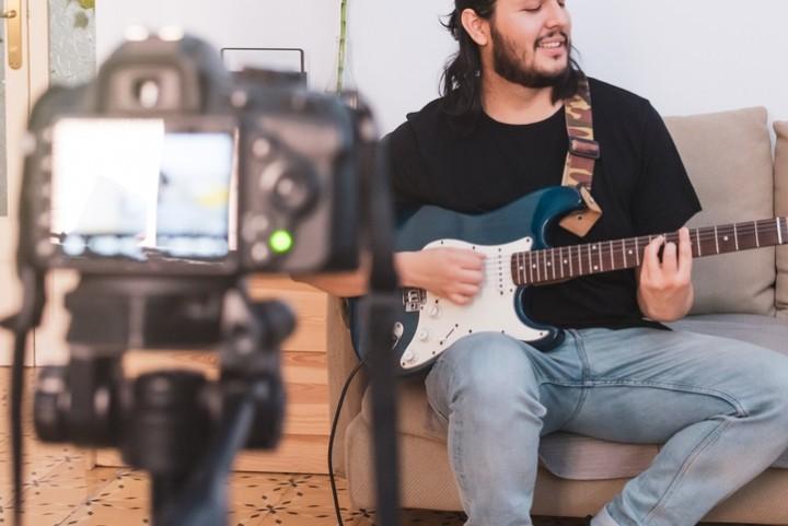 Man filming playing guitar