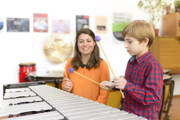 female percussion teacher teaching young male student in the classroom