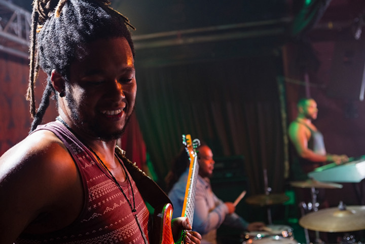 happy musician playing a guitar with others in a band