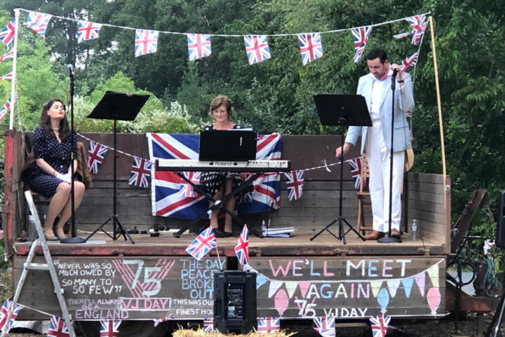 A tractor trailer is decked out with bunting, and three socially-distanced performers with music stands and a digital piano stand are situated on top of it.  There are chalk-written messages on the side of the trailer with slogans marking 75 years of VJ Day.
