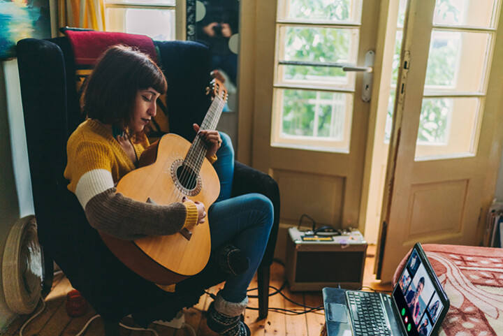 A woman plays her guitar and looks at some people she is video chatting to.