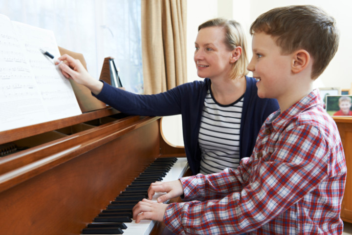 Female teacher points at music for child on piano