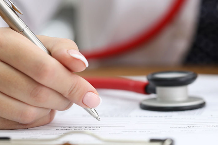 A hand writes notes with a stethoscope nearby