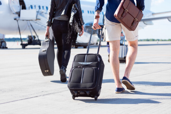Two travellers walking towards a plane one carrying a guitar case the other luggage