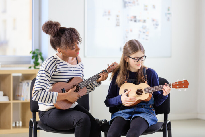 one to one music tuition. teacher teaching student guitar