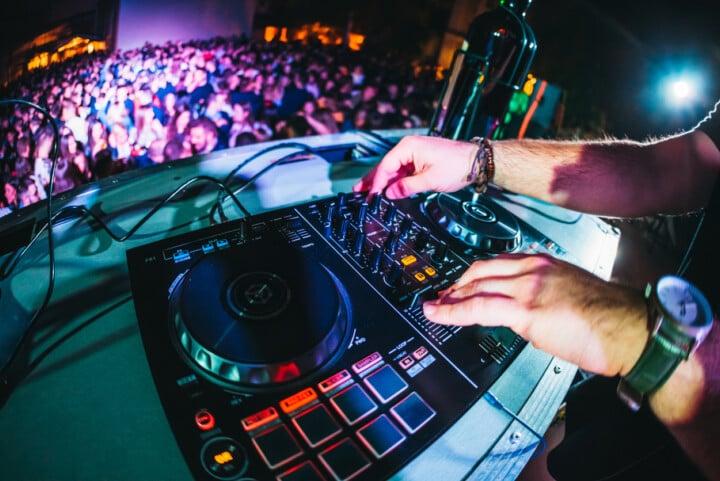 A DJ at the decks in a dance club