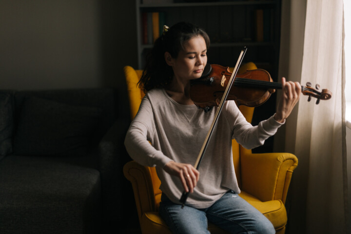 woman playing the violin while sitting on a yellow chair