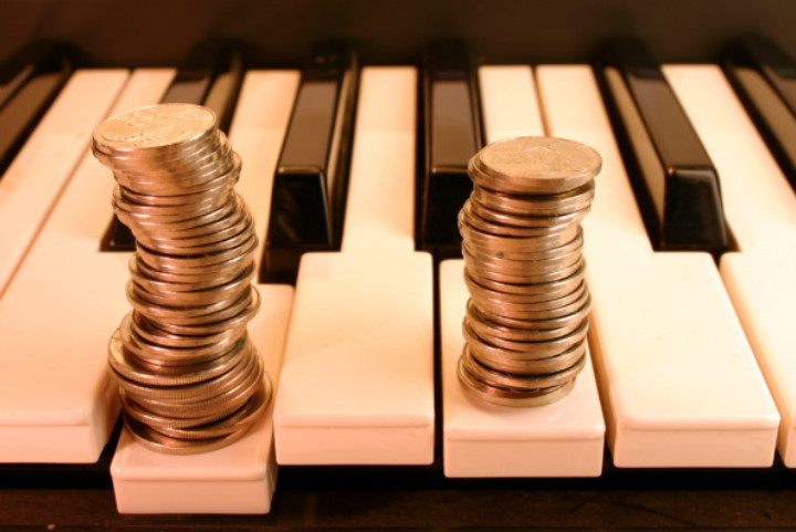 Two columns of coins stacked on a piano