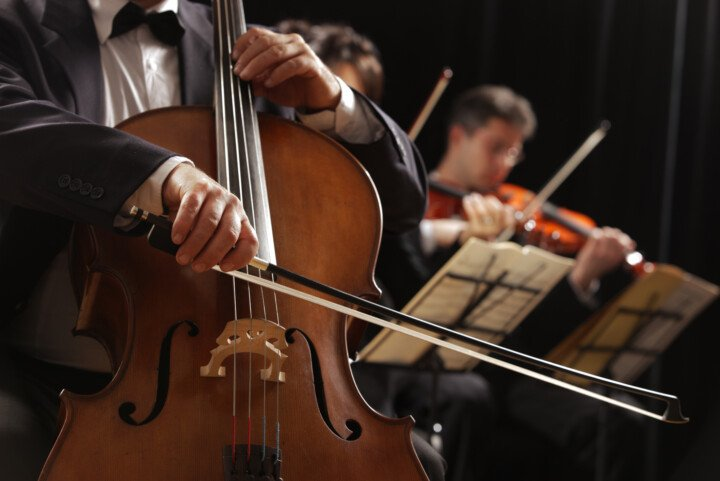 close up of orchestra musicians playing string instruments