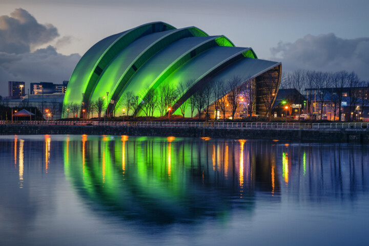 The SECC venue in Glasgow, lit up in green and reflected in the river.