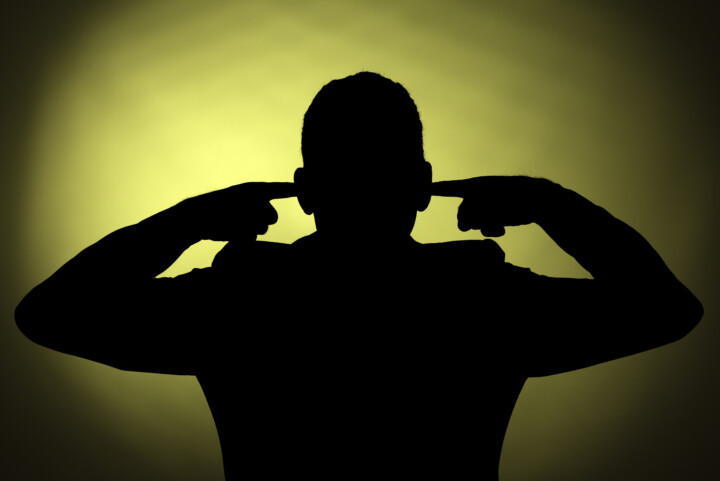 A silhouette of a man with his fingers in his ears.