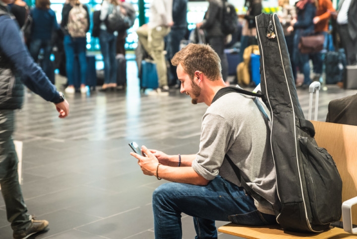 Man with a guitar on his back, in an airport