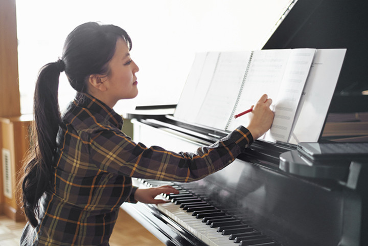 piano teacher writing on music