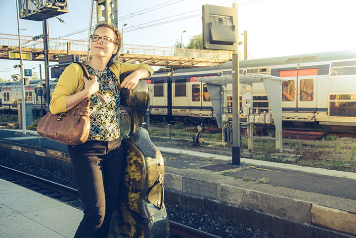 A musician waits on a train station with her case