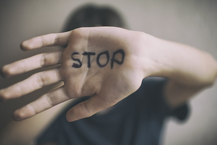 human with palm up with the word 'stop' written on the palm