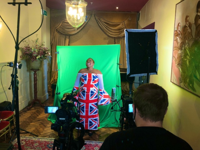 Alison Buchanan stands in front of a green screen wearing a Union flag inspired dress