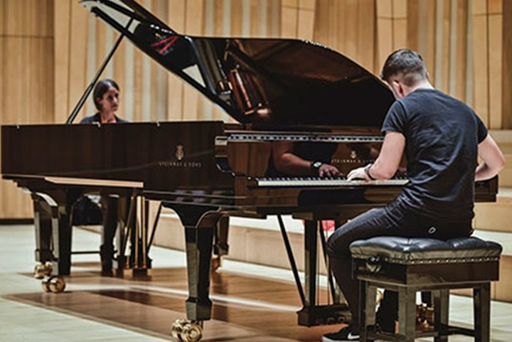 Two musicians wearing black play two grand pianos facing each other