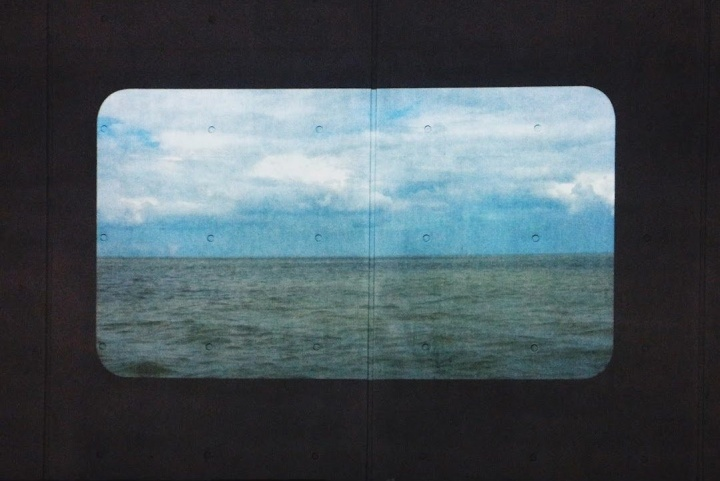 A vista of a blue sky over a green landscape as seen projected from a vintage video reel