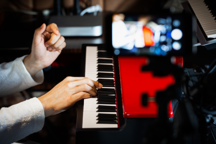 man playing keyboard and filming