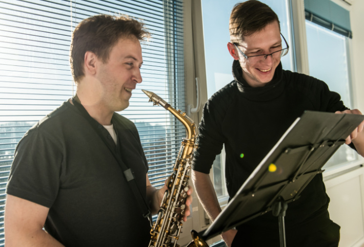 A young man in a saxophone lesson with his teacher