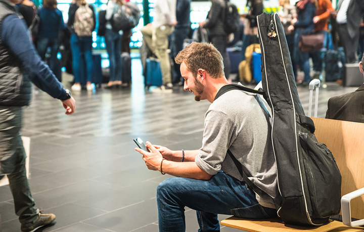 Man at airport with guitar looks at phone