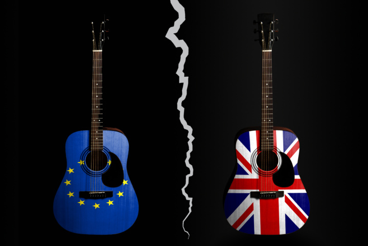 Two guitars decorated in the flags of the EU and of the UK are separated by a large white crack