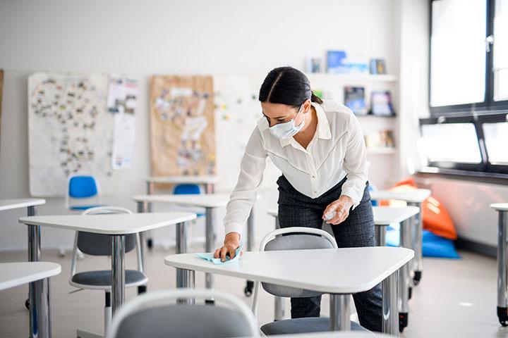 A female teacher wipes a desk