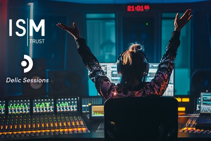 A woman in a recording studio holds her hands up in celebration