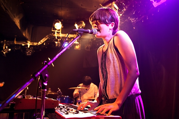A young female musician on stage singing and playing keyboard. A drummer is also seen in the background playing on the same stage.
