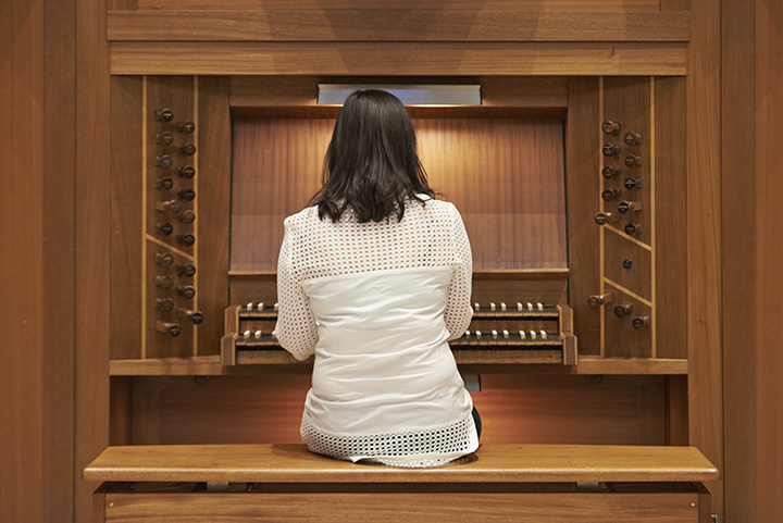 A woman plays the organ with her back to the camera