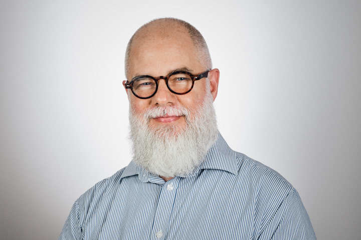 John Robinson wearing round glasses