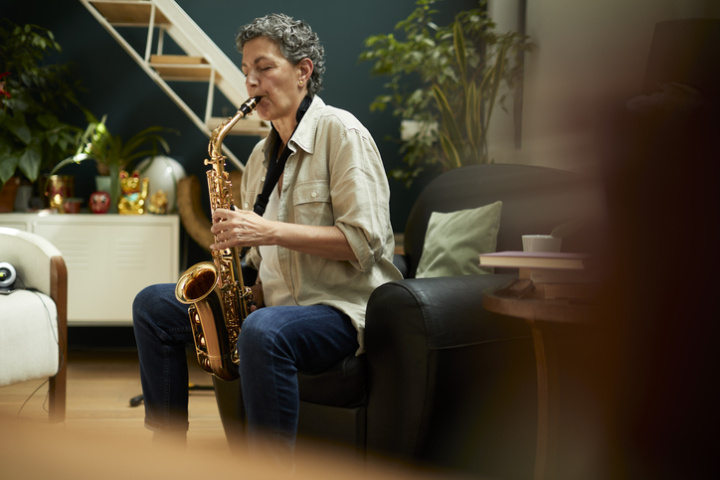 A woman sits on the sofa and plays her saxophone.