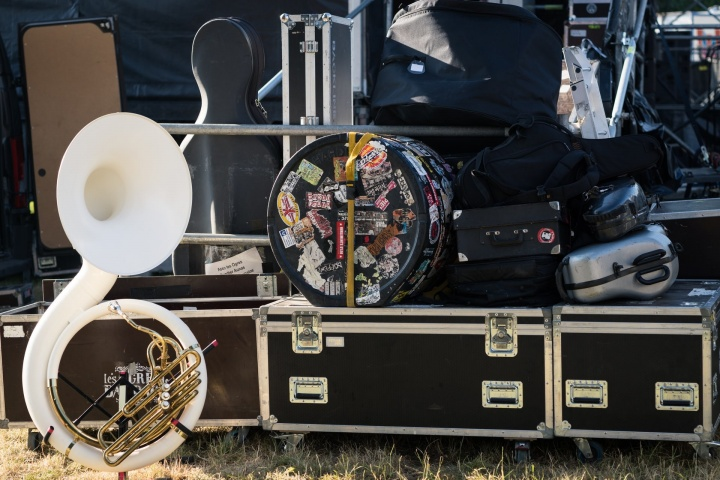 A series of flight cases and instruments stacked on grass as part of a tour