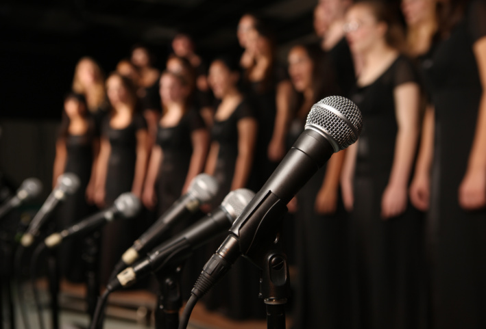 microphones in foreground with singing choir in background