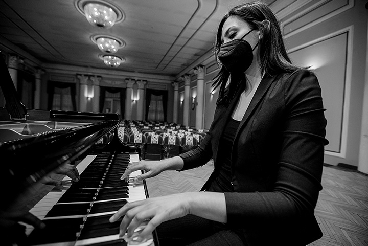 A woman in a mask plays the piano